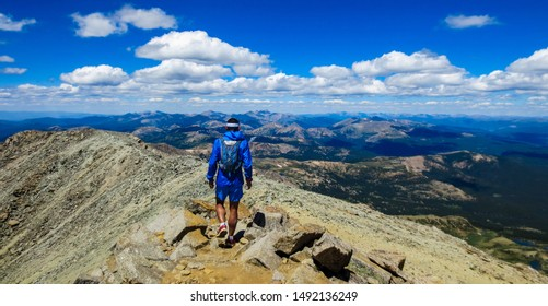 Unidentifiable male, athletic hiker/trail runner on a narrow path at the peak of Mt. Massive, a 14er in Colorado, USA, with breath-taking views in the background.