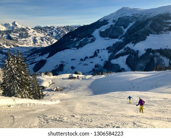 Unidentifiable man and woman downhill skiing on wide piste in the ski resort of Saalbach-Hinterglemm in Austria.