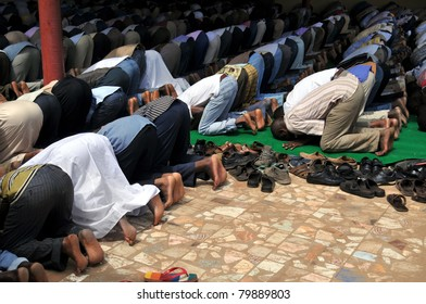 Unidentifiable muslim men praying, facing the holy city of Mekka, at a courtyard of a mosque in Sudan