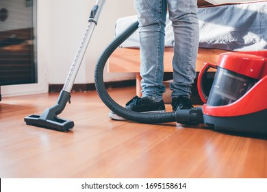 Unidentifiable people indoors at home using vacuum cleaner - houseworks, cleanliness, hoovering concept