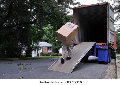 An unidentifiable person is carrying a heavy moving box up a ramp into the back of a moving truck (altered features, not recognizable), on a summer day in typical suburban America