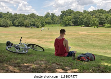 Unidentifiable person reading a book in Piedmont Park on a sunny day with a bike and backpack and other people playing in the distance on the green grass