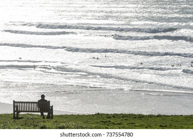 An unidentifiable person sat on a bench, silhouetted against the afternoon sun reflected from the breaking waves on a beach