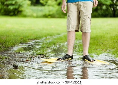 Unidentifiable person in shorts and scuba flippers standing in middle of large puddle on turf grass