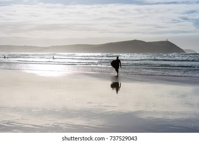 Unidentifiable silhouetted surfer with board on the beach at Polzeath in North Cornwall, UK. Sun flare catches the surf and wet sand.
