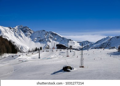 Unidentifiable skiers at ski resort in Pila, Valle d'Aosta, Italy with chairlift and mountain backdrop and copy space - winter sports concept