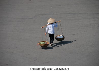 Unidentifiable street vendor selling items in Vietnam by carrying goods on traditional pole