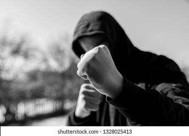 Unidentifiable teenage boy attacking with hes bare hands, focus on the fist in black and white, conceptual image of juvenile delinquency.