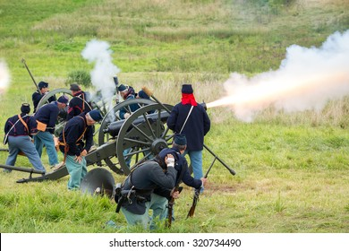 Unidentifiable union soldiers fire a cannon during a reenactment of the Civil War Battle of Gettysburg.