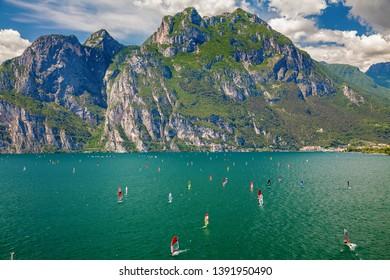 unidentifiable windsurfers surfing on a Garda lake near Torbole and Riva del Garda, Italy