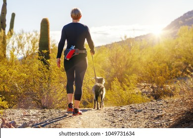 Unidentifiable woman walking a dog on a hiking path in Mountain View Park in Phoenix, Arizona
