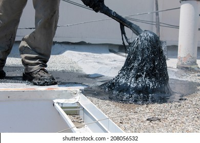 """Unidentifiable workers use """"Hot Tar"""" aka """"Hot Mop"""" to lay down Molten Tar, Asphalt Sheets and Pea Gravel on a Flat roof on a Hot Summer day in Southern California. Roofs are important on houses"""