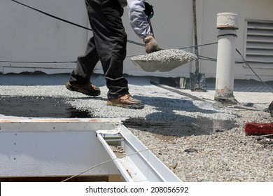 "Unidentifiable workers use ""Hot Tar"" aka ""Hot Mop"" to lay down Molten Tar, Asphalt Sheets and Pea Gravel on a Flat roof on a Hot Summer day in Southern California. Roofs are important on houses"