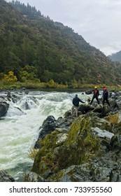 Unidentified Adventurous Men Standing On Rocks Near Rainy Falls, Oregon.