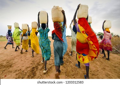 Unidentified African women walking with water containers on their heads in a village near the city of Tanzania, Dar Es Salaam. Tanzania, Dar es Salaam Africa. June 17, 2017: