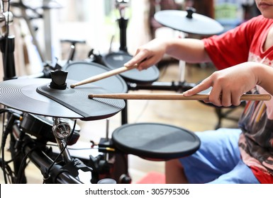 Unidentified Asian boy play electronic drum in music room
