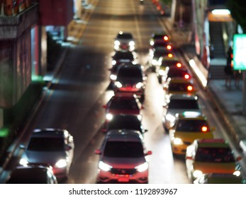 unidentified automobile, cars stay waiting in rows at an ample waiting for green traffic light in urban downtown zone blur defocused peacefully night life scene background on a dark street