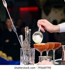 Unidentified barman adding foam in a martini glass with cocktail, shallow dof