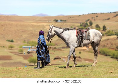 Unidentified basotho man with his horse wearing traditional blanket - Lesotho