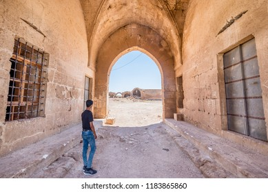 Unidentified boy stands in front of Han El Ba'rur,a Seljuk caravanserai in Harran,Sanliurfa,Turkey.