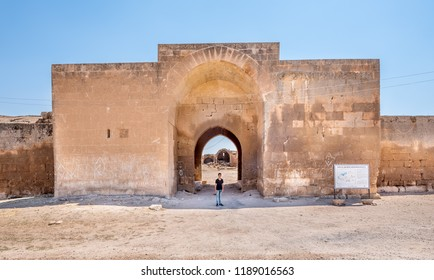 Unidentified boy stands in front of Han El Ba'rur,a Seljuk caravanserai in Harran,Sanliurfa,Turkey.20 July 2018