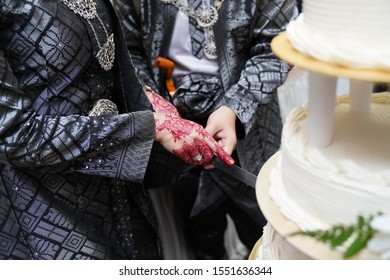 Unidentified bride and groom slice a white wedding cake during Malay wedding ceremony. Close-up of hand with red henna and wedding ring.
