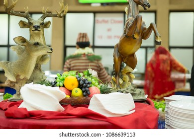Unidentified bride and groom taking food from the buffet on wedding day.
