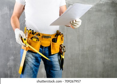 unidentified builder standing in white gloves with a tool belt with construction tools and holding roulette and the project plane against grey background. DIY tools and manual work concept