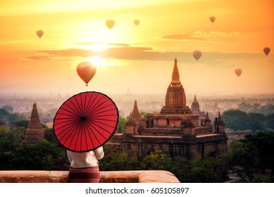 Unidentified Burmese woman holding traditional red umbrella and looks at Hot air balloon over plain of Bagan in misty morning, Mandalay, Myanmar