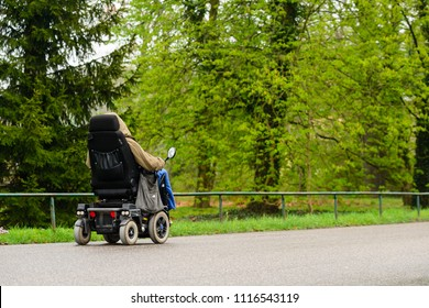 Unidentified disabled person in an electric wheelchair outdoors