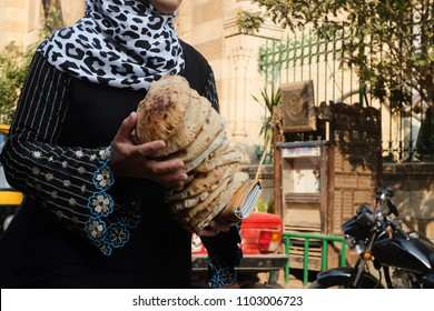 An unidentified Egyptian girl holds traditional flat breads in Cairo - Egypt