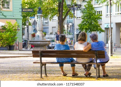 Unidentified elderly women are sitting on a wooden bench in the middle of the city center of a German city and chat about different things and spend time together