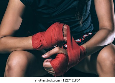 Unidentified face of woman boxer wrapping her hand in boxing arena sport. Texture effect may visible. Selective focus