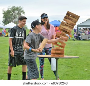 Unidentified family playing Jenga at the Denver Botanic Gardens Lavender Festival on July 15, 2017. In Denver, Colorado. It was an event to promote the use of lavender.