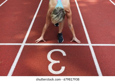 unidentified female athlete launching off the start line in a race