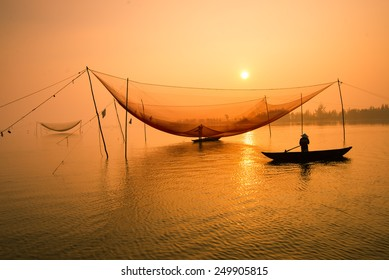 Unidentified fisher man check his nets in early morning on river in Hoian, Vietnam. Hoian is recognized as a World Heritage Site by UNESCO.