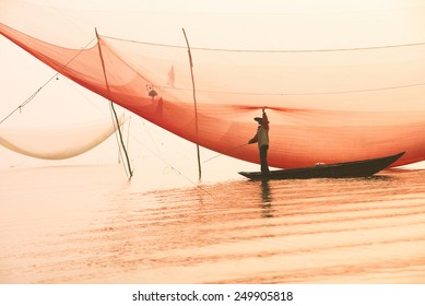 Unidentified fisherman checks his nets in early morning on river in Hoian, Vietnam