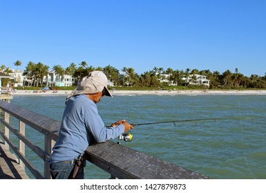 Unidentified Fisherman holding fishing rod over railing wears long bill sun cap on Naples Pier in Florida. Cloudless blue sky, sandy beach and high end oceanfront housing in background.