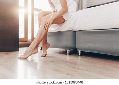 Unidentified girl in lingerie is stroking delicate skin of legs while sitting on bed. Pretty young woman enjoys smoothness and health of legs after removing unwanted hair. Beauty Shugaring Concept