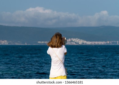 An unidentified girl looking through a tower viewer at sea in Nessebar, Bulgaria. A girl looking through a coin binocular, free use viewer, outdoor viewer