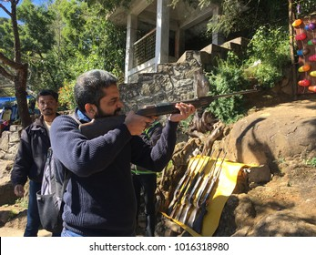 Unidentified guy practicing shooting with balloons in kodaikanal, Tamil Nadu, India. 26th December 2017