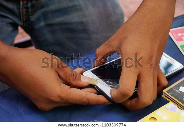 Unidentified hand are installing tempered glass  on smart phone