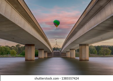 Unidentified hot air balloon passing over the commonwealth bridge Canberra with capital hill in the distance.