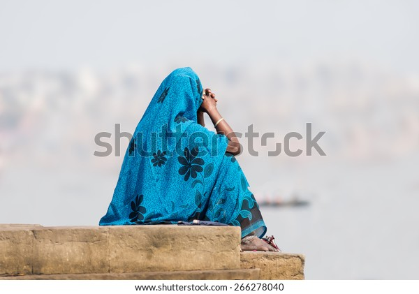 An unidentified Indian woman wearing a blue sari sitting at the ghats on the banks of The Ganges in Varanasi, India.