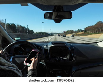 Unidentified lady is looking at the phone while driving on highway, nice clear blue sky day with few traffic. Steering wheel is on the left