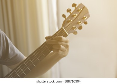 Unidentified male play guitar with left arm closeup with curtain background with  soft orange light