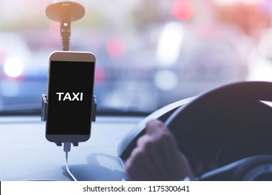 An unidentified man is driving Taxi. Image taken from back seat with taxi word on phone screen.
