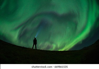 Unidentified man enjoying the Northern Lights (Aurora Borealis) during a Solar Storm. Low light condition.