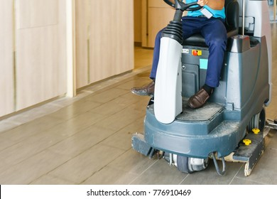 unidentified man operates rider floor Scrubber Machine at supermarket