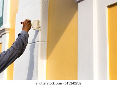 Unidentified man painting with brush on the building wall outside